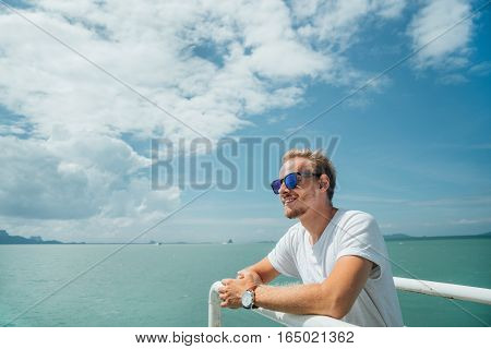 Portrait of a young successful man on the background of sky and sea landscape. Blonde with glasses in white shirt leaning on the railing of the ship. Cruise.