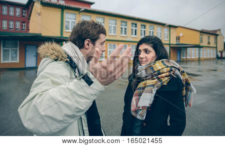 Portrait of dissapointed woman listening arguments of young man during a hard quarrel outdoors. Couple relationships and problems concept.