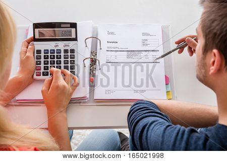 Close-up Of Couple Calculating Family Budget Invoices Insurance And Tax Using Calculator At Home