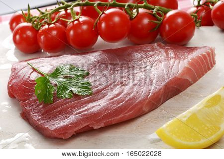 Crop view of raw tuna fillet piece with cherry tomatoes and lemon on the table surface