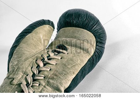 Crop view of single vintage boxing leather glove with laces laying on white surface