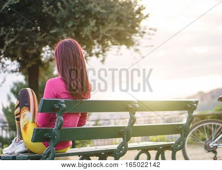 Sporty woman sitting on a bench admiring the view in a beautiful park outdoor - Depressed girl sitting alone watching the city from the hills - Sportswoman work out taking a break - Soft focus