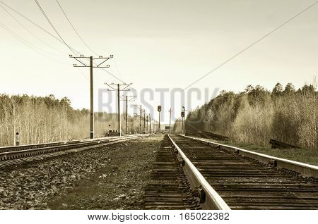 Modern electificated railroad track close to vintage one with wooden sleepers. Toned.