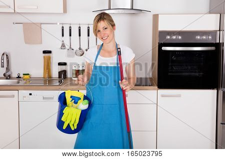 Cleaning Service Professional Housemaid Holding Gloves And Equipment In Kitchen At Home