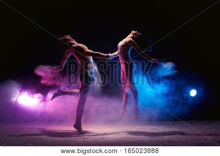 Contemporary art - full length shot of young graceful dance couple  performing in dark studio or scene in cloud of powder