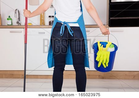 Close-up Of Housemaid Service Woman With Cleaning Equipment Standing In Kitchen