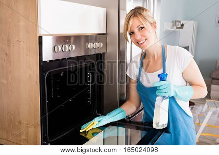 Young Woman Cleaning Microwave Oven With Spray Bottle And Rag