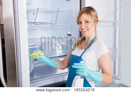 Young Smiling Professional Janitor Woman Cleaning Empty Refrigerator In Kitchen