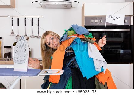 Young Woman Holding Help Flag With Behind Of Clothes Near Ironing Board At Home