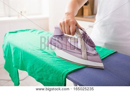 Close-up Of Young Woman Hand Ironing Green T-shirt At Home