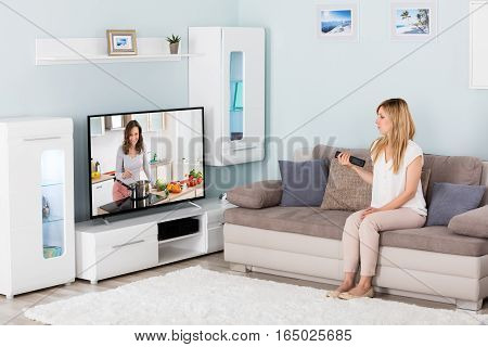 Young Woman Watching Cooking Show On Television At Home