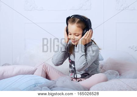 Child schoolgirl sitting on a bed and listening to an audiobook. The concept of childhood education and music.