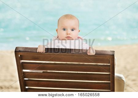 Portrait Of An Innocent Baby Leaning On Wooden Bench On Beach