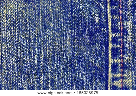 Textured blue denim background in run-down jeans, toned image