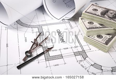 Construction drawings, drawing instruments, financing of the construction, packs of dollars, building drawing on paper, a set of drawing tools, blueprints rolled up into a roll