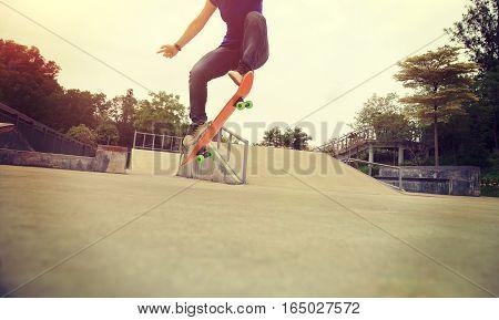 young skateboarder practice ollie trick at skatepark