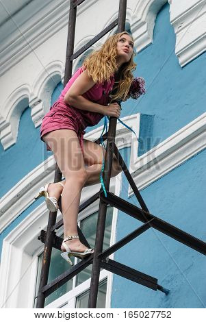 Young attractive woman with bouquet on fire escape stair