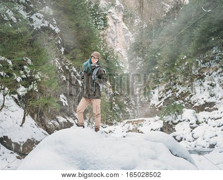 Smiling young woman with backpack standing in winter gorge looking at camera