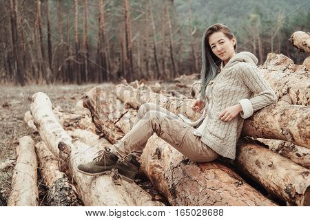 Beautiful young woman sitting on stack of felled tree trunks in the woods