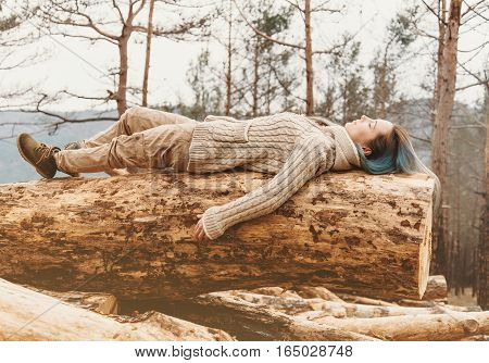 Beautiful young woman with closed eyes lying on fallen tree trunk in the woods outdoor