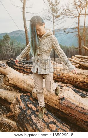 Young woman walking on stack of felled tree trunks in the forest