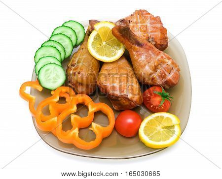 smoked chicken legs with vegetables and lemon on a plate on a white background. horizontal photo.