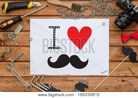 Father's Day flat lay mock up template with hand lettering greeting note and male accessories: tools, chain, photo camera, bow tie and funny photo booth paper mustache