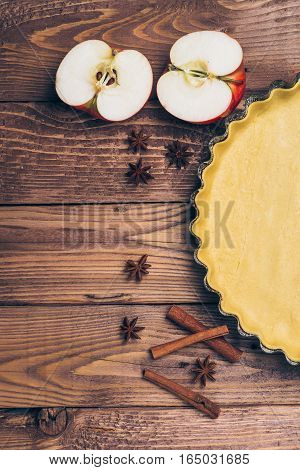 Ingredients for apple tart apples and cinnamon on the rustic wooden background.