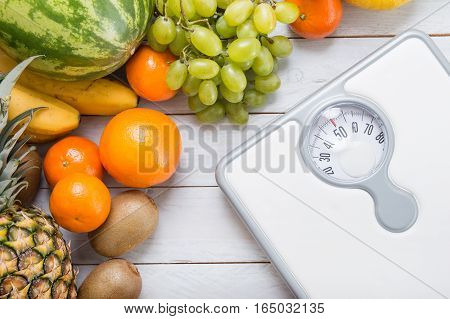 Stack Of Fruits And White Weight Scale On Wooden Board. Concept Of Diet And Healthy Lifestyle