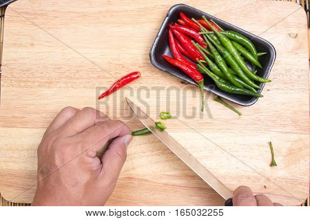 Hand cutting Hot Chili Peppers on wooden broad