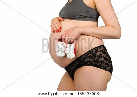 Pregnant woman with a pair of baby shoes in front of her belly