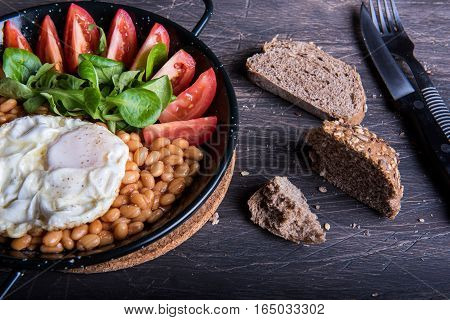 Breakfast with beans, tomatoes, eggs and bread. Crumbs on the table