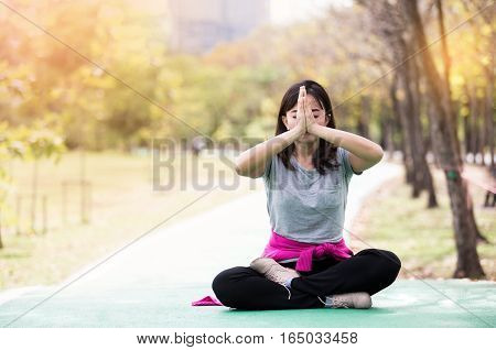 Beautiful mature woman posing in sit meditation at nature garden. Relax and active lifestyle concept soft focus in vintage tone