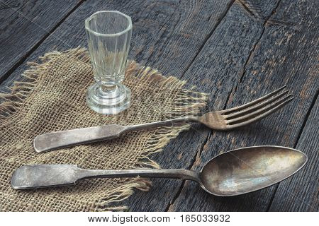 The spoon fork and an empty glass on a rustic napkin