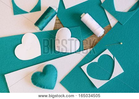 Small stuffed hearts toys. Hearts made of felt, thread, felt sheets, needle on wooden table. Simple handmade crafts for Valentine's day, mother's day, wedding. Top view