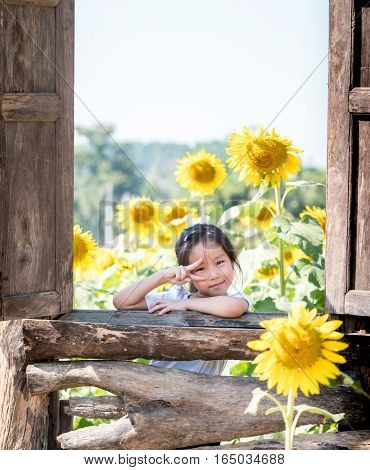 portrait of Asian adorable little girl in the field of sunflowers (Helianthus annuus)