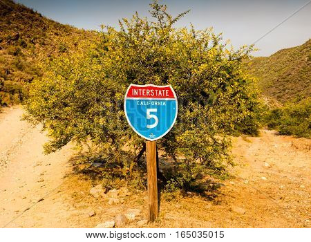 Quriky idea of a California interstate 5 traffic sign in front of desert thorn tree with gravel road fork in South Africa
