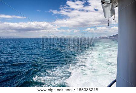 Wake of motorboat speeding away from coast on ocean