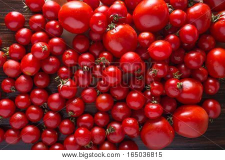 Tomatoes of different varieties. Red tomatoes Tomatoes background. Fresh tomatoes Healthy food concept. Colorful festive still life. Loosely laid tomatoes in different positions.