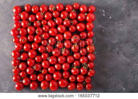 Cherry tomatoes in a square form. Colorful tomatoes Tomatoes background. Fresh tomatoes Healthy food concept. Colorful festive still life. Loosely laid tomatoes in different positions.