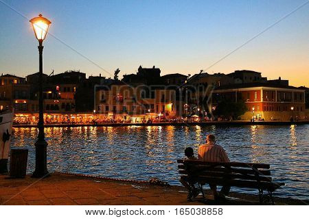 Sunset view of a grandfather tellking stories to his nephew in front of  Xania's harbour, Crete, Greece. This suggestive place is also called the Little Venice
