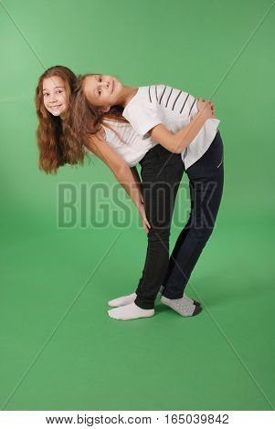 Two friends school girls back to back isolated on green