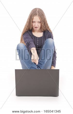 Student teenage girl sitting on the floor with laptop isolated on white