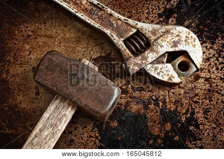 Rusted adjustable wrench and maul hammer on metal.