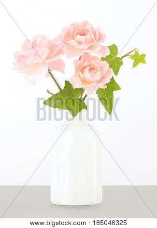 Close up of fresh cut pink miniature garden roses arranged in a vase with green ivy