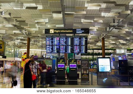 Singapore - January 8, 2017: Couple visitors taking selfie photo with Departure Board in Changi Airport. Departure Hall, it is one of the largest transportation hubs in Asia.