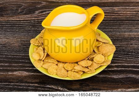 Yellow Jug Milk In Saucer With Corn Flakes On Table