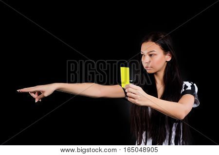 Beautiful Soccer Referee shows yellow card. Isolated over black background