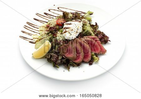 salad of veal cheese and red pepper on black plate. restaurant food on a white plate isolated background