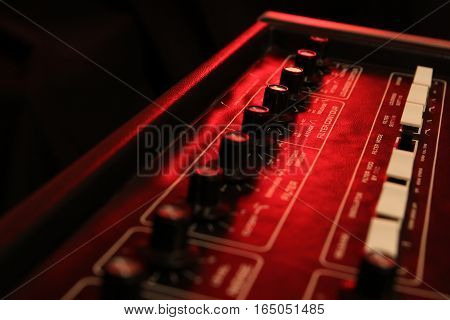 Controls Of A Retro Analog Music Synth In Red Light